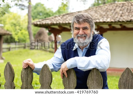 old man with gray hair and beard standing in front of his old house behind an wooden fence - stock photo