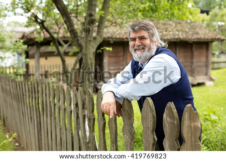 old man with gray hair and beard standing in front of his old house behind an wooden fence
