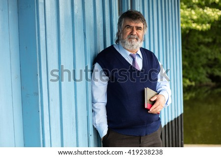 old man with gray hair standing on a porch next to a lake with a book - stock photo
