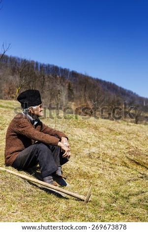 Old man with hat having a break from work, resting on the field - stock photo