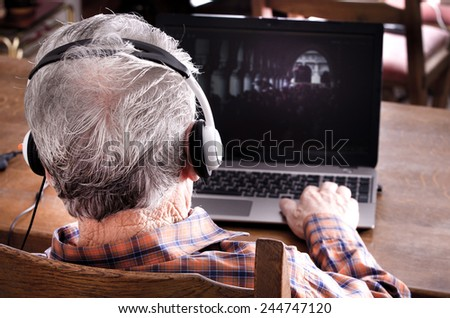 Old man with headset looking at laptop - stock photo