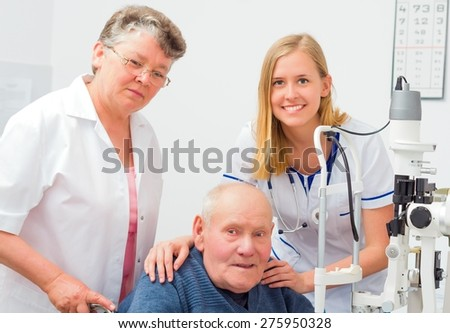 Old man with nurse and doctor at an optical exam. - stock photo