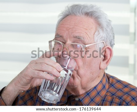 Old man with reading glasses holds and drinks glass of water - stock photo