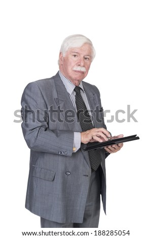 old man with silver white gray hair in a double breasted suit standing and typing on a tablet looking at the camera in studio on a white background - stock photo