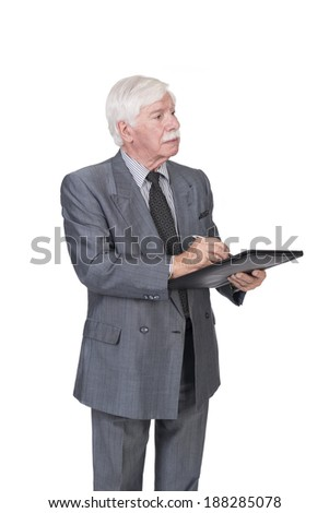 old man with silver white gray hair in a double breasted suit standing and writing on a note pad  or completing a form  - stock photo