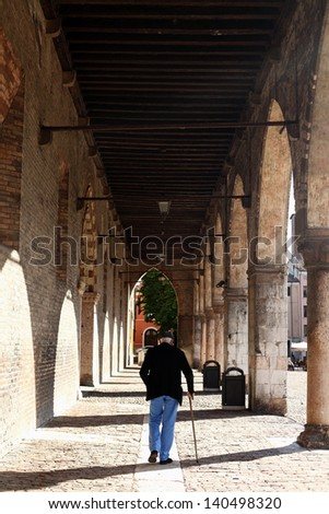 Old man with stick at the gonzaga palace in the center of Mantua, Italy - stock photo
