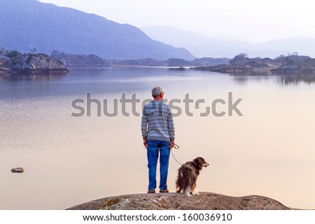 Old man with the dog at the lake in Killarney National Park - stock photo