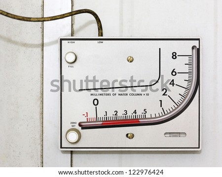 Old manometer installing on white wall - stock photo