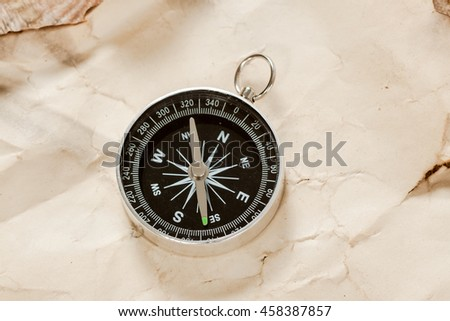Old map with compass on old wooden background.