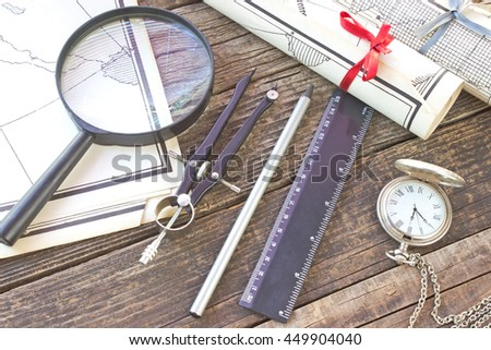 Old Maps with tools on wooden background - stock photo