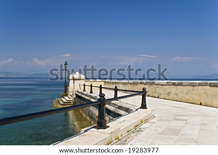 Old marina made by marble in Corfu greece - stock photo
