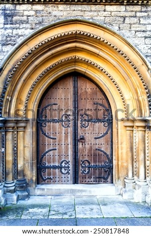 Old massive church door with arch - stock photo