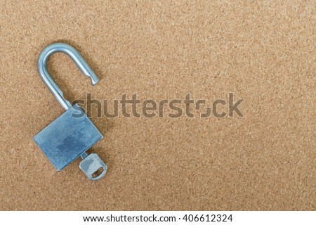 Old master key and key lock on cork board background