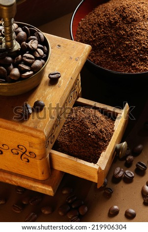 Old mechanical coffee grinder, ground coffee, coffee beans - stock photo