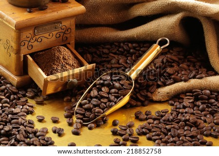 Old mechanical coffee grinder, ground coffee, coffee beans, jute sack, golden scoop - stock photo