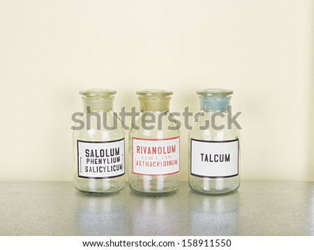 old medical glass bottles on the metal shelf - stock photo