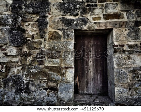 old medieval abbey wall with gate - stock photo