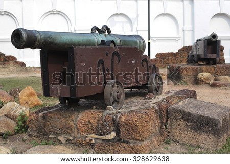 Old medieval artillery canon before a brick wall - stock photo