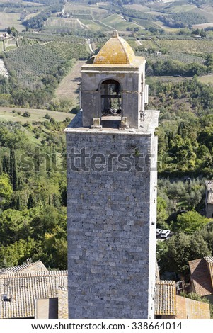 Old medieval bell tower in front of the olive groves in Tuscany - stock photo
