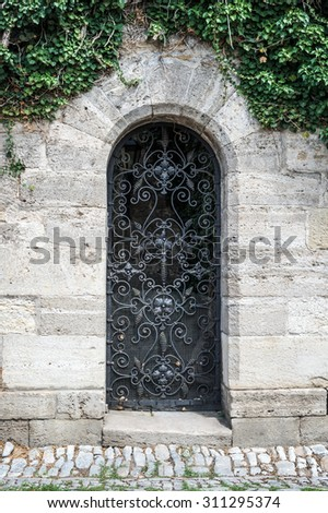 Old medieval black metal door with curved bar and light stone wall