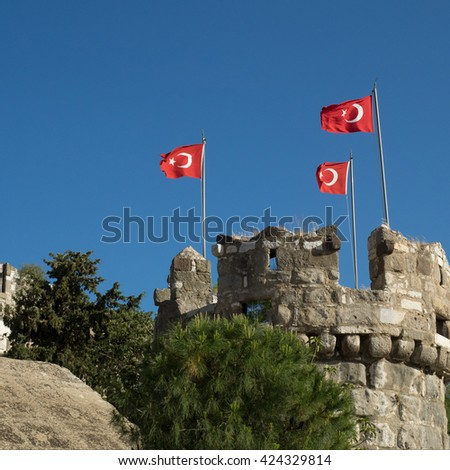 Old medieval fortress in Turkey. Ancient tower with Turkish flags. Crusaders castle in Bodrum. - stock photo