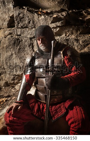 Old medieval King in armor with sword is sitting on furs near the camp fire - stock photo