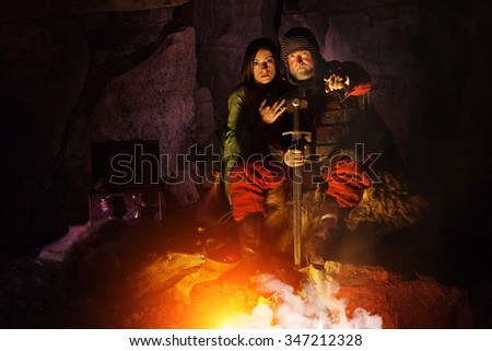 Old medieval King in armor with sword is sitting on furs near the camp fire. Young princess on the background.