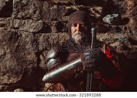 Old medieval King in armor with sword on the rocks background. Focus point on the face.