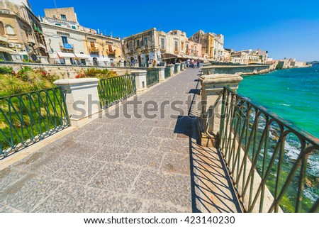 Old medieval mediterranean small town beach promenade with the azure blue sea in the background, Sicily, Italy - stock photo