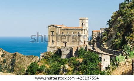 Old medieval mediterranean small town on the top of the mount with church and the blue sea in the background, Sicily, Italy - stock photo