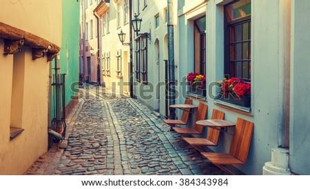 Old medieval  morning narrow street in Riga, Latvia. Retro styled. - stock photo