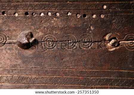 Old medieval style wooden background texture with a weathered cracked panel of wood with iron studs, nails and hand engraved decorative circles or spirals - stock photo