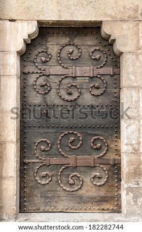 Old medieval wooden door with metal motif decoration in Rocamadour, France - stock photo