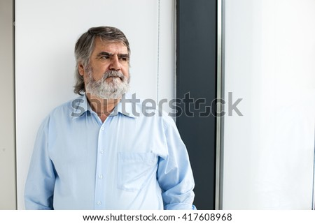 old men in blue shirt and gray beard standing next to a big window thinking at something
