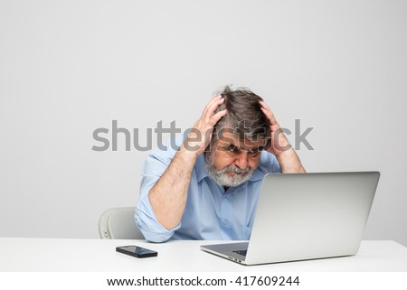 old men in blue shirt having problems in using a laptop