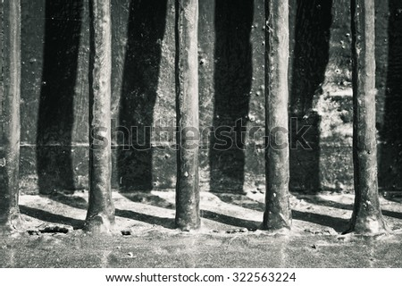 Old metal bars with shadows, as a background, in black and white tones