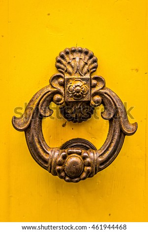 Old metal door knob on yellow background.