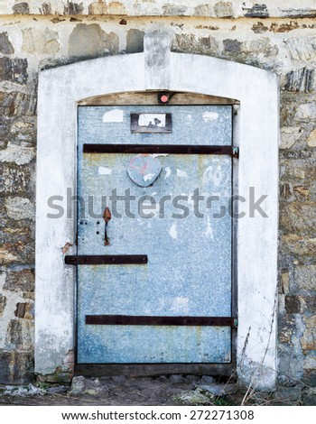 Old metal door with different locks in a stone wall - stock photo