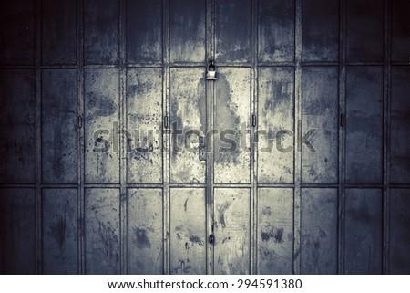 Old metal door with padlock. Grey scale. - stock photo