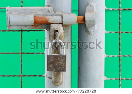 Old metal doors of factory are locked with a padlock. - stock photo