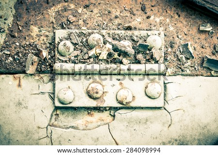 Old metal hinge and rust and rivet on old metal sheet of auto part in horizontal view high contrast style. Grunge or retro or old background for industry design. - stock photo