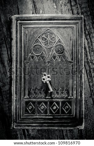 Old metal key lying on a decorated ancient book in black and white - stock photo
