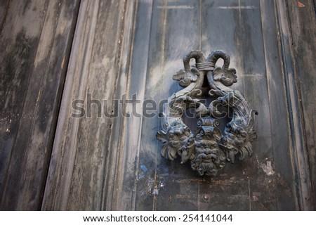 Old metal knocker on a door - stock photo