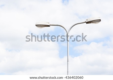 Old metal light pole with blue sky white cloud background.