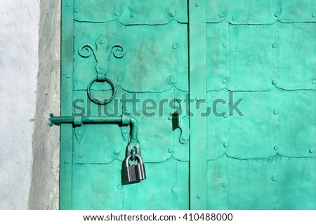 Old metal light turquoise door with rivets, plates and aged metal door handle in the form of stylized lily. Architectural detailed vintage background.  - stock photo
