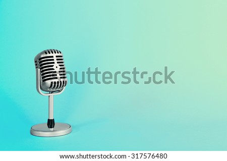 Old metal microphone on turquoise background - stock photo