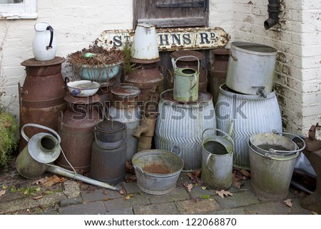 Old metal milk churns, watering cans, buckets etc - stock photo