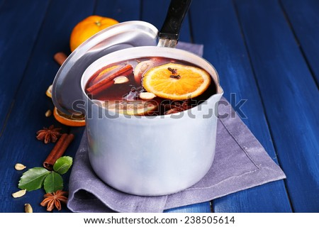 Old metal pan of tasty mulled wine on wooden table - stock photo