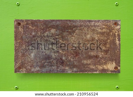Old metal plate on a green wall - stock photo