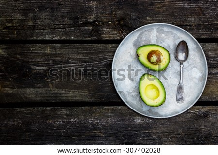 Old metal plate with halved avocados on rustic wooden background with space for text. Top view. Food or cooking concept. - stock photo